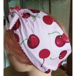 side view of tied pink large red cherry contrast red white polka dot wired hairband