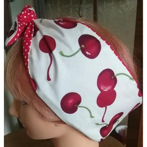 side view of tied white large red cherry contrast red white polka dot wired hairband