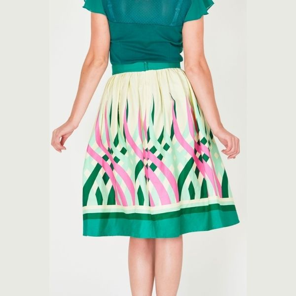 close up view of mid length 50's styledswing skirt with swirls of pink and green with a bold green hem border
