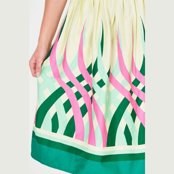 close up of mid length 50's styledswing skirt with swirls of pink and green with a bold green hem border