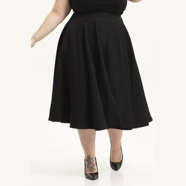Front view of black circle swing skirt hem fall below the knee with pockets on a plus size model
