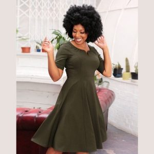Army green 50's style swing dress elbow-length sleeves, and fitted waist that flares out into a skirt that falls approximately just below the knees. A round neckline features a small v cut-out at the front centre, accentuated by a piece of boning, and a little gathering around the neck. Fastening with a centre-back zip and hook and eye.